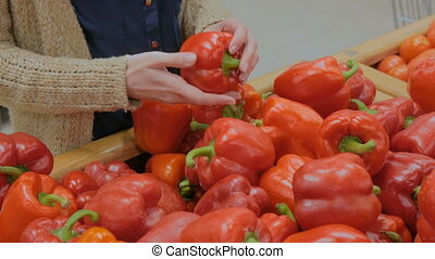 Woman buying fresh red bell peppers at grocery store
