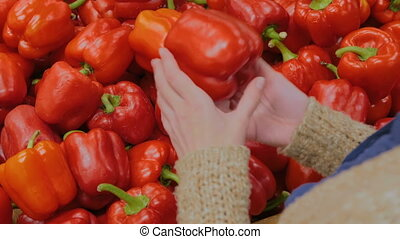 Woman buying fresh red bell peppers at grocery store - Woman...