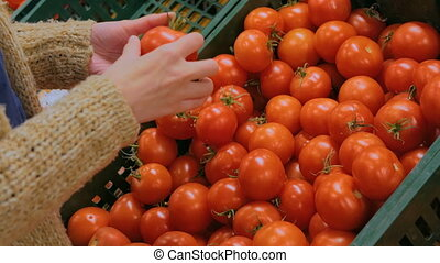 Woman buying fresh red tomatoes at grocery store
