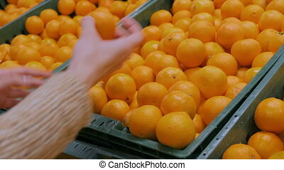 Woman buying fresh tangerines at grocery store