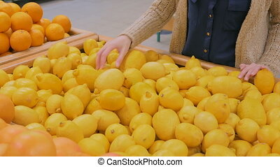 Woman buying fresh yellow lemons at grocery store