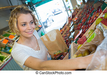 woman buying fruits and vegetables at local food market