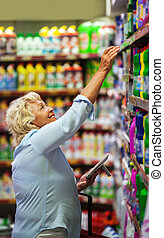 Woman buying household detergents in the shop