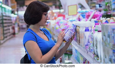 Woman buying laundry detergent in the supermarket -...