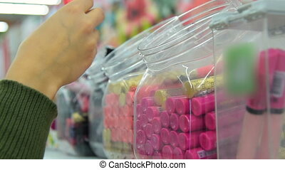 Woman buying lip gloss in the store - Woman taking a lip...