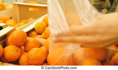 Woman buying mandarins at the store