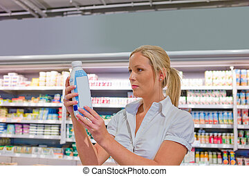 woman buying milk at the grocery store