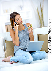 woman buying online on laptop with credit card at home