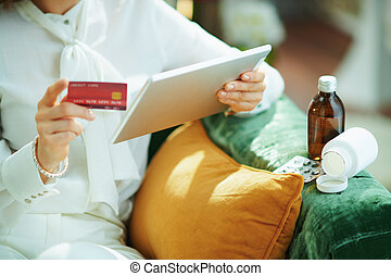 woman buying pharma on tablet PC at home in sunny day