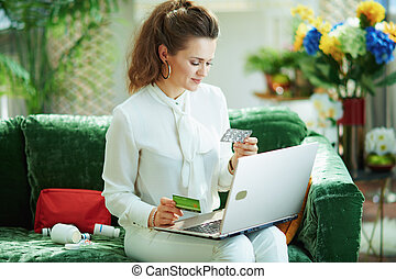 woman buying pharma using laptop in modern house in sunny day