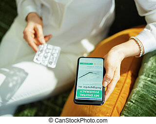 woman buying pharma using phone in house in sunny day