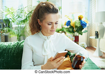 woman buying pharma using phone in modern house in sunny day