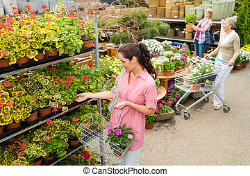Woman buying potted flower in garden center - Woman buying...