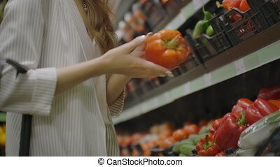 Woman Buying red Pepper in Supermarket. Female Hand Choosing...