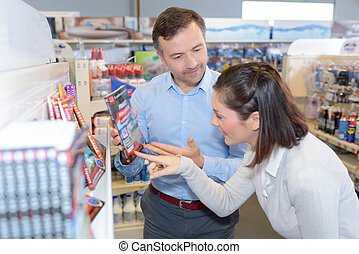 woman buying roadmap of france in hardware store