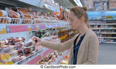Woman buying sausage at supermarket