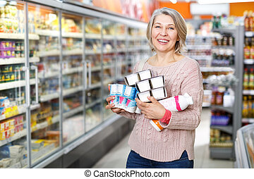 Woman buying some foodstuffs at grocery store
