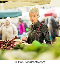 Woman buying vegetable at local food market. - Woman buying ...