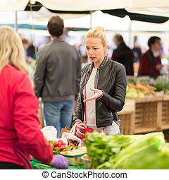 Woman buying vegetable at local food market. - Woman buying...