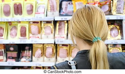 woman buys a sausage in a supermarket, 4k, slow-motion.