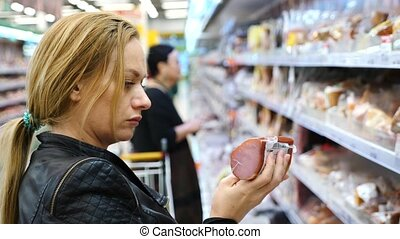 woman buys a sausage in a supermarket, 4k, slow-motion. -...