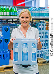 woman buys bottled water at the grocery store