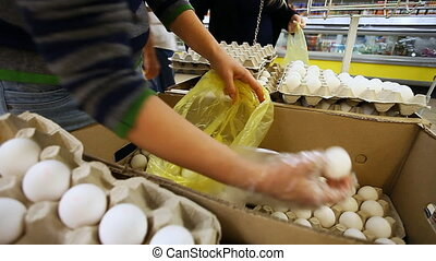 woman buys eggs at the supermarket, blurred background
