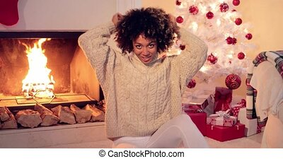 Woman by fireplace and white christmas tree - African...