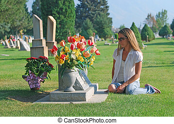 Young woman sitting near grave in cemetery.