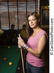 Woman by pool table. - Portrait of woman standing by...