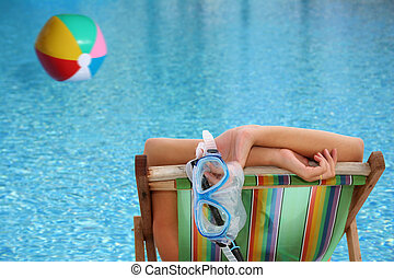 Woman by Pool - Woman in deckchair by blue pool with...