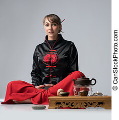 Woman by table laid for chinese tea ceremony