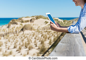 woman by the beach reading on tablet-pc