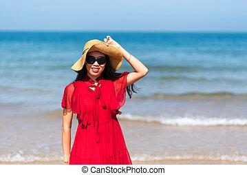 Woman by the seaside wearing red dress