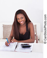 Woman Calculating Finance At Home