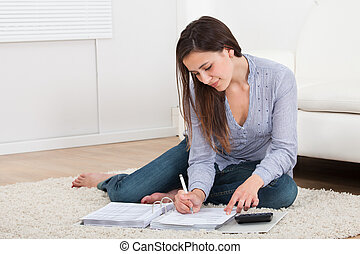 Woman Calculating Home Finances On Rug - High angle view of ...