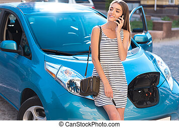 Woman calling and standing near her car