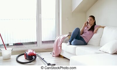 woman calling by smartphone after cleaning home - cleaning,...