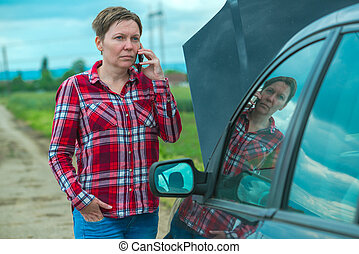 Woman calling car repair service from counrty road