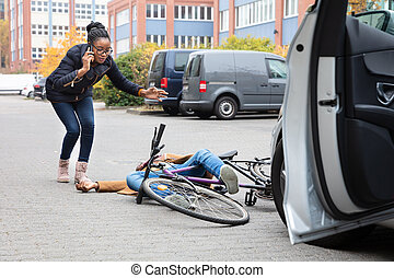 Woman Calling For Help Near Unconscious Cyclist Lying On Street