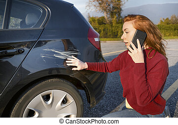 Woman calling insurance service after car crash