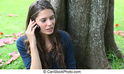 Woman calling leaning against a tre