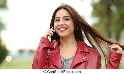 Front view of a candid woman calling on phone looking at you in a park. Slow motion