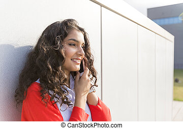 Woman calling on phone standing next to a  wall
