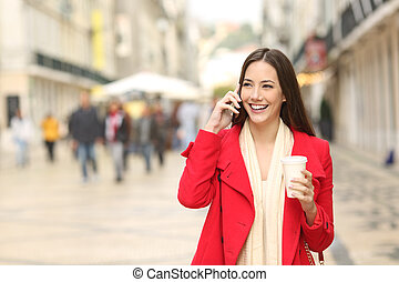 Woman calling on phone walking in the street