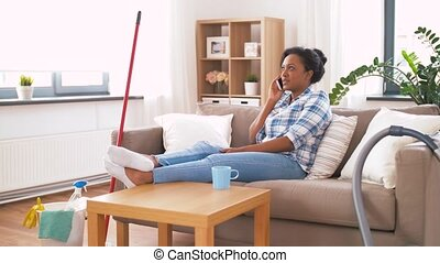 woman calling on smartphone after home cleaning - household...
