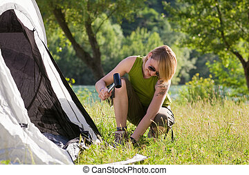woman camping - Young woman fastening tent and holding ...