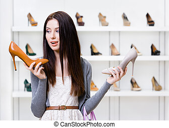Woman can't choose high heeled shoes - Woman keeps two high...