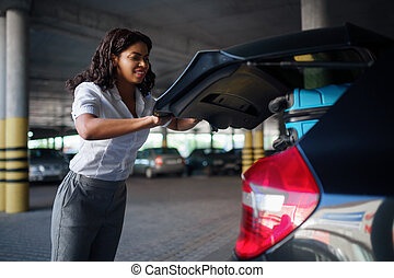 Woman can't close trunk with suitcases, parking