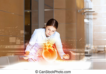 Image of attractive woman cardiologist examining virtual heart